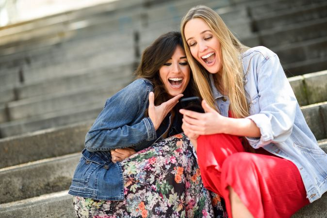 two-young-women-looking-at-some-funny-thing-on-their-smart-phone-outdoors-sitting-on-urban-steps-friends-girls-laughing-1702523-1446136